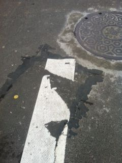 Pavement tar and line looks like koala hugging tree