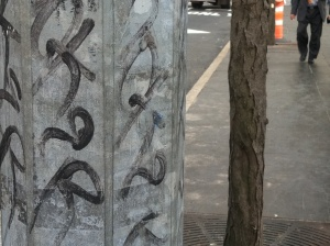 Metal street pole with graffiti mimics neighboring tree trunk and bark