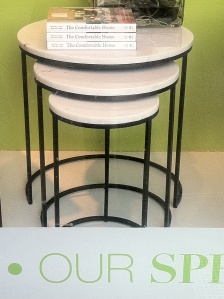 Store window with 3 round nesting tables and rectangular books